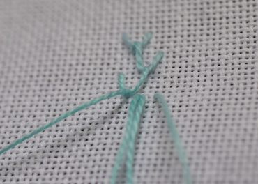 Step 4 in working single feather stitch