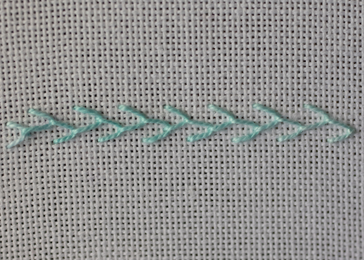 Row of single feather stitch worked on evenweave